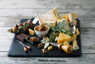 Poster Delicious cheeses on a board with honey, nuts on a white backgro