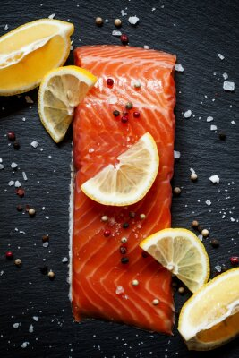 Poster Delicious salmon fillets with lemon, sea salt and pepper on a da