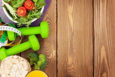 Poster Dumbells, tape measure and healthy food over wooden table