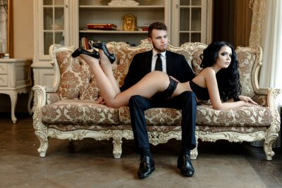 Poster Fashion photo romance of sexy lovers couple. woman with black curly hair in black underwear and man wearing suit