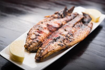 Poster Fish on the grill with lemon on white plate