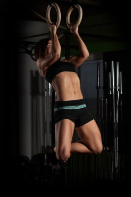Poster Fit young woman on gymnast rings