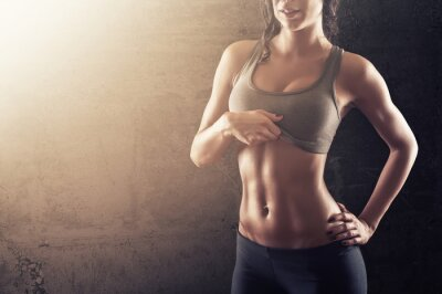 Poster Fit young woman showing her abs