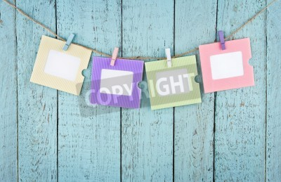 Poster Four empty colorful photo frames or notes paper hanging with clothespins on wooden blue vintage shabby chic background
