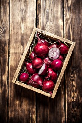 Poster Fresh red onion in an old box.