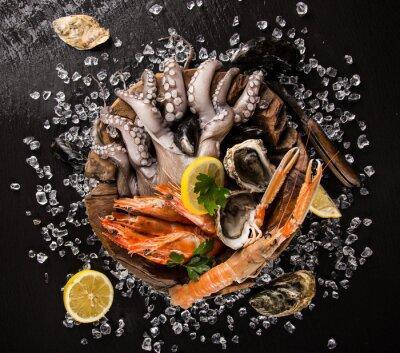 Poster Fresh seafood on black stone.