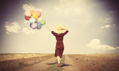 Poster girl with multicolored balloons and bag