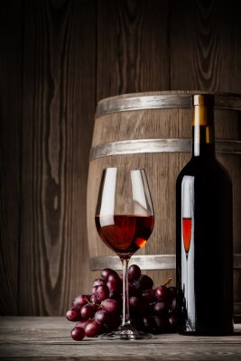 Poster Glass of red wine with bottle and keg standing