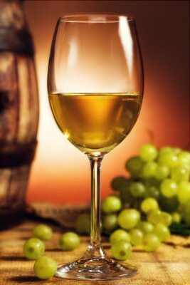Poster Glass of white wine in front of green grapes and old barrel
