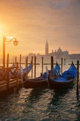 Poster Gondolas by Saint Mark square during sunrise with San Giorgio di Maggiore church in the background in Venice Italy
