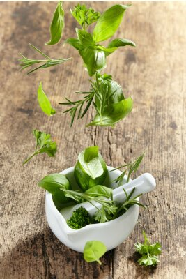 Poster green herbs falling into mortar and pestle