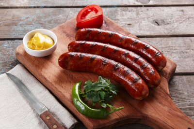 Poster Grilled sausage on a wooden board with sauce and vegetables