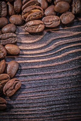 Poster Heap of coffee beans on vintage wooden board top view