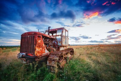 Poster ld rusty tractor in a field on sunset