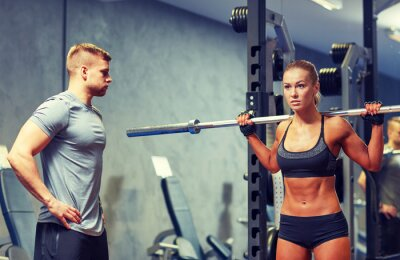 Poster man and woman with barbell flexing muscles in gym