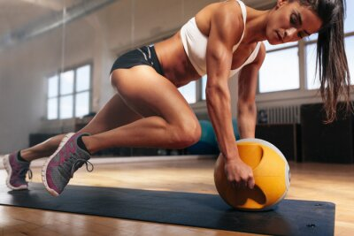 Poster Muscular woman doing intense core workout in gym