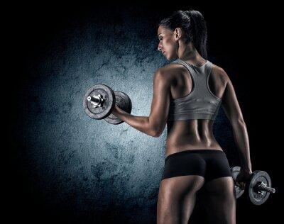 Poster Muscular woman in studio on dark background