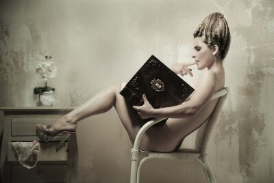 Poster Naked woman sitting in a chair reading a book indoors