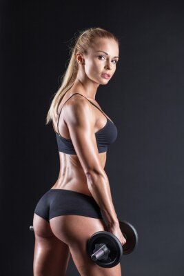 Poster Portrait of a beautiful girl athlete with a dumbbell in studio