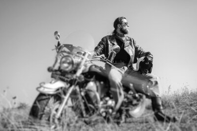 Poster Portrait of a young man with beard sitting on his cruiser motorcycle and looking to the sun. Man is wearing leather jacket and blue jeans. Low point of view. Tilt lens blur effect. Black and white