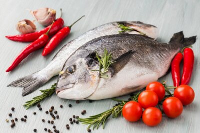 Poster Raw fresh dorado fish with vegetables and spices