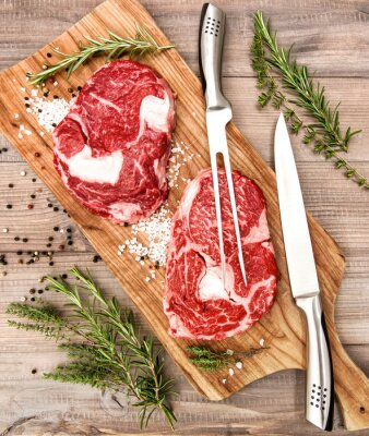 Poster Raw fresh meat Ribeye Steak with herbs and spices on wooden desk