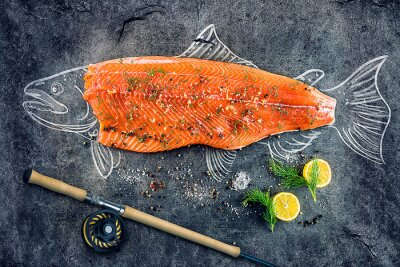 Poster raw salmon fish steak with ingredients like lemon, pepper, sea salt and dill on black board, sketched image with chalk of salmon fish with steak and fishing rod