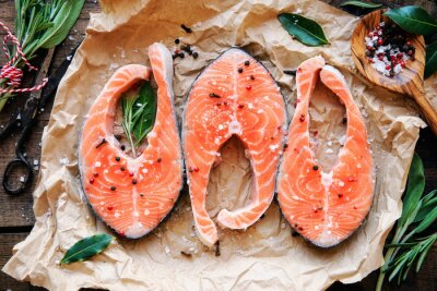 Poster Raw salmon steaks with fresh herbs, salt and pepper corns. Overhead view