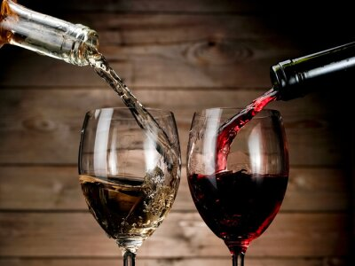 Poster Red and white wine pouring on wood background