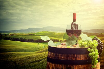 Poster Red wine bottle and wine glass on wodden barrel. Italy