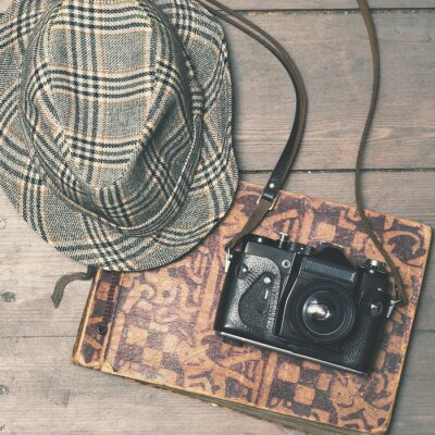 Poster retro camera with vintage trilby hat and photo album on wooden b