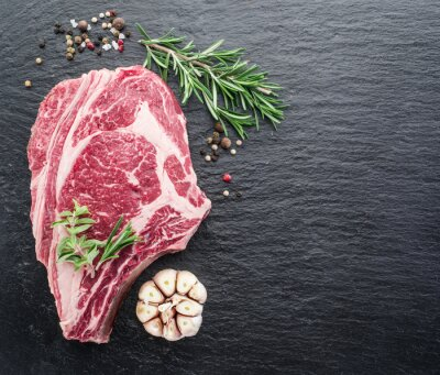 Poster Rib eye steak with spices on the black background.