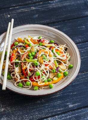 Poster Rice noodles with vegetable stir fry on the ceramic plate on dark wooden background