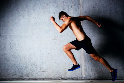 Poster Runner sprinting against concrete wall in garage