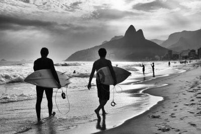 Poster Scenic black and white view of Rio de Janeiro, Brazil with Brazilian surfers walking along the shore of Ipanema Beach