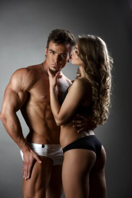 Poster Sexual bodybuilder hugs girl possessively