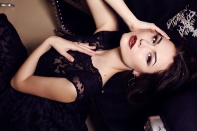 Poster sexy  woman in black dress posing in luxurious interior