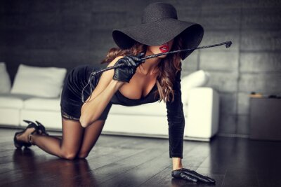 Poster Sexy woman in hat and whip kneeling on floor indoor