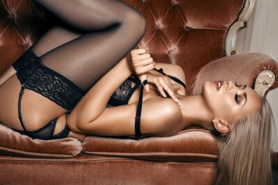 Poster sexy woman in seductive black lingerie lying on a couch in stockings
