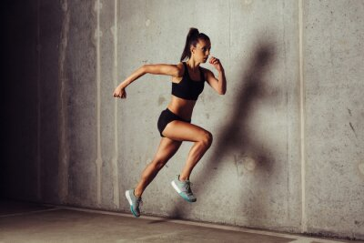 Poster Slim attractive sportswoman running against a concrete background