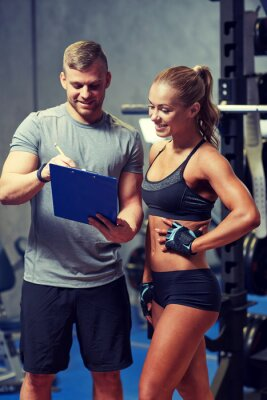 Poster smiling young woman with personal trainer in gym