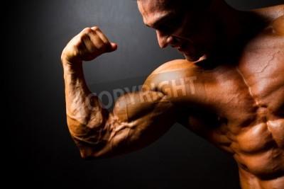 Poster strong bodybuilder posing on black background