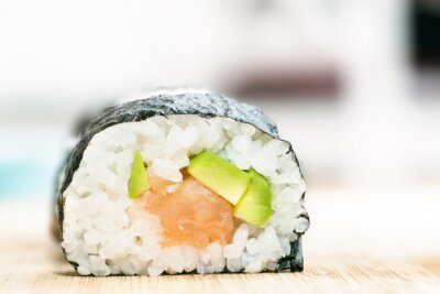 Poster Sushi with salmon, avocado, rice in seaweed and chopsticks on wooden table