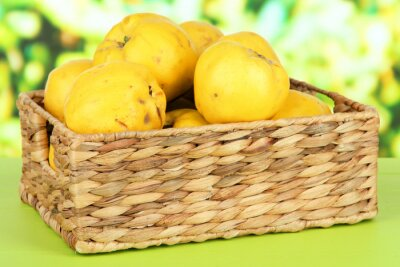 Poster Sweet quinces in wicker basket on table on bright background