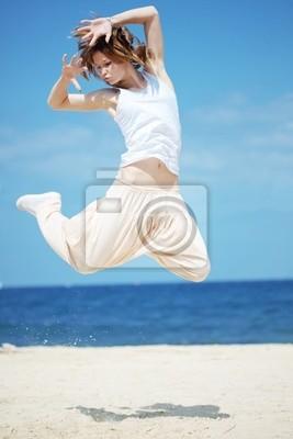 Teenage girl dancing hip-hop and jumping on beach, summer series