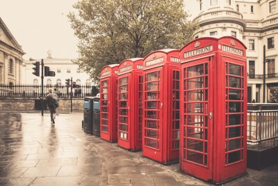 Poster Vintage style  red telephone booths on rainy street in London