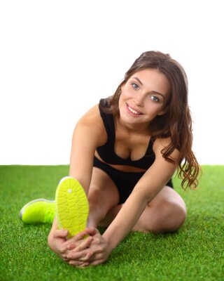 Poster Woman doing stretching exercises on the green grass