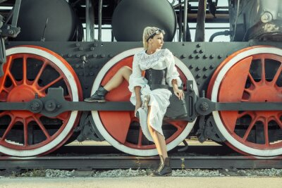 Poster Woman in the vintage dress is sitting on the locomotive's wheel.