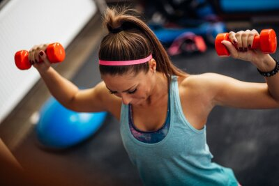 Poster Woman lifting weights and working on her shoulders at the gym