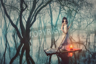 Poster Woman on a raft with a lantern floating on a pond in a misty forest. Fairy tale woman in a long dress.